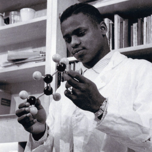 Black and white photo of man holding a scientific instrument