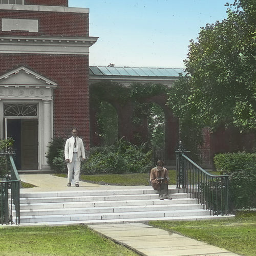 Old photo of two people in front of a building on campus