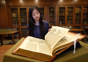 Researcher reading a larger book