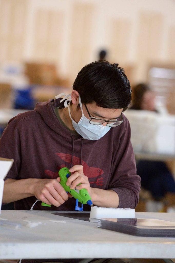 masked student using a hot glue gun